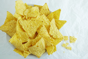 Traditional Mexican tortilla chips or nachos on white paper background