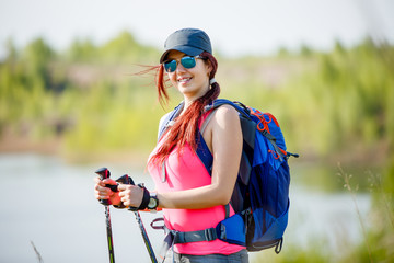 Photo of sports girl with walking sticks on background of lake and green vegetation