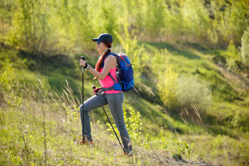 Photo of smiling sportswoman with walking sticks and backpack