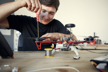 Photo of engineer with screwdriver fixing square copter at table