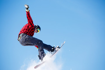 Photo of young sportive man jumping with snowboard