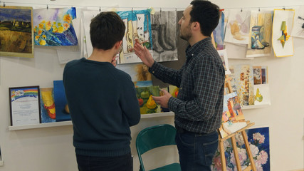 Two young men looking at paintings in art studio