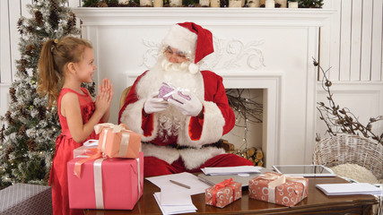 Busy Santa sorting chidlren's letters while cute little helper bringing him a gift