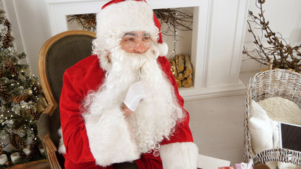 Santa Claus finishing writing and checking his letter to a kid