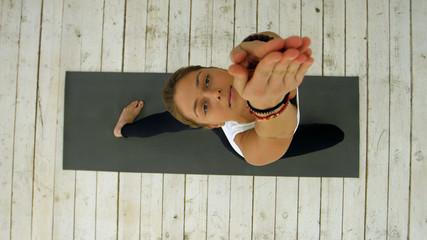 Young beautiful woman doing yoga exercise, sun salutation pose