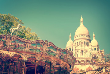 Vintage carousel and the Basilica of the Sacred Heart in Montmartre, Paris France