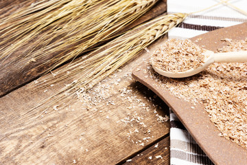 Wheat bran in wooden spoon on wood table - healthy eating concept