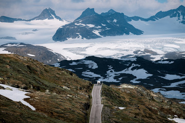 Caravan on a mountain road in Norway with glacier in the background