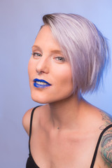 Portrait of a young, attractive woman with blue lipstick