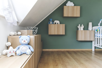 Stylish scandinavian newborn baby room with toys, teddy bear, cotton lamps and star. Modern interior with green background wall.