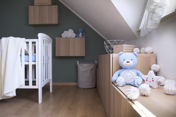 Stylish scandinavian newborn baby room with toys, star lamp and teddy bear. Modern green background wall.