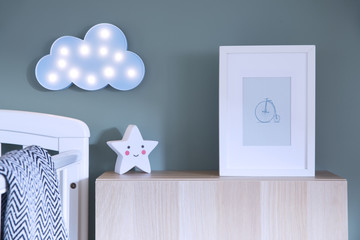 The modern scandinavian newborn baby room with mock up poster frame, blue cloud and star lamp. Sunny and bright interior.