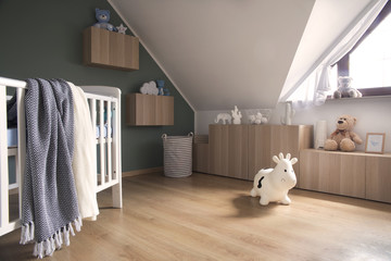 Stylish scandinavian newborn baby room with toys, teddy bears, happy cow and baby cot. Modern green background wall.