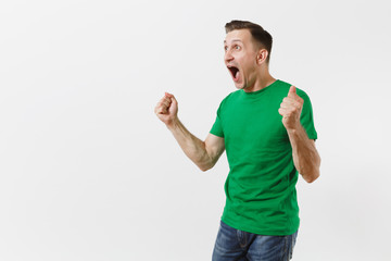 Overjoyed European young man, football fan in green t-shirt support his favorite team, rejoices over goal, isolated on white background. Sport, play football, cheer guy, fans people lifestyle concept.