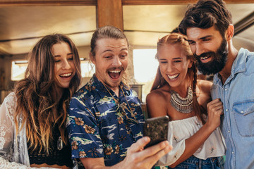 Laughing friends taking selfie with cellphone.