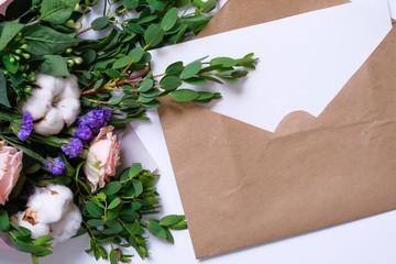 Mockup with postcard, flowers bouquet, kraft envelope.