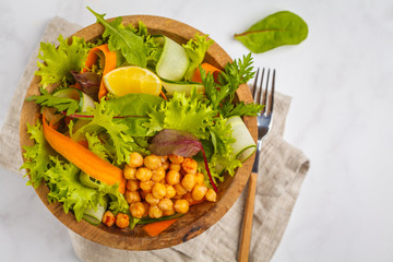 Summer bright vegetable salad with chickpeas in a wooden bowl. Healthy vegan food concept.