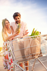 Young happy couple pushing shopping cart