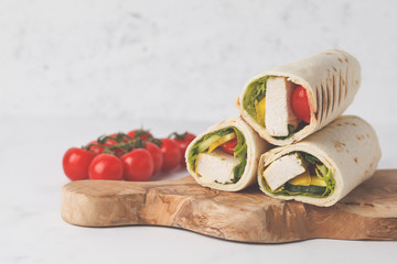 Grilled tortilla wraps with chicken and vegetables  on wooden board