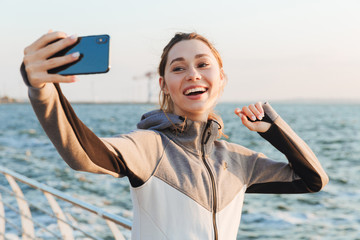 Happy young sportswoman taking selfie with mobile phone