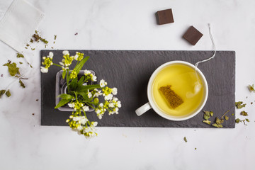Green (herbal, white) tea with dark chocolate on white background. Flat lay food