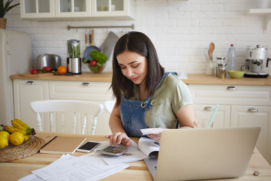 Indoor shot of attractive young female doing calculations, managing home budget, sitting at kitchen table and smiling. Pretty girl paying domestic bills online, using laptop computer and calculator