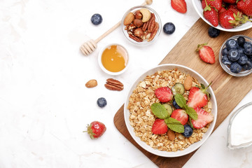 Serving option of granola bowl with mix of nuts, cereals, fruits and berries, greek yogurt. Healthy vegetarian breakfast, organic strawberry, blueberry, mint, almond. Close up, top view, background.