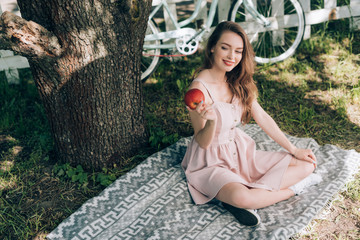 smiling attractive woman with ripe apple in hand resting on blanket under tree at countryside
