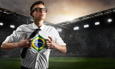 Brazil soccer or football supporter showing flag under his business shirt on stadium.