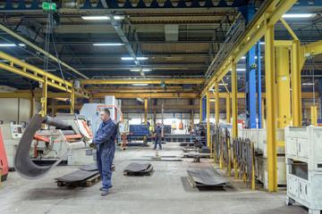 Workers with steel bending machines in engineering factory