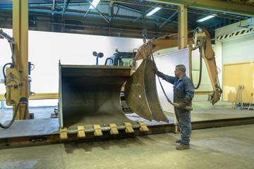 Worker assembling digger bucket in engineering factory
