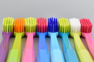 Multicolored toothbrushes stock images. Morning hygiene. Bathroom accessories images. Toothbrush on a gray background. Toothbrush on a silver background with copy space for text