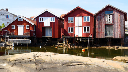 Red wooden boathouses on a sunny day in Smogen on the Swedish west coast.