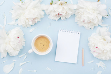 Morning coffee cup for breakfast, empty notebook and white peony flowers on blue pastel table top view. Woman working desk. Flat lay.