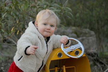 Petit bébé garçon dans son jardin avec la voiture. jeux d'enfants
