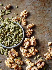 Pumpkin seeds in bowl and walnuts on table