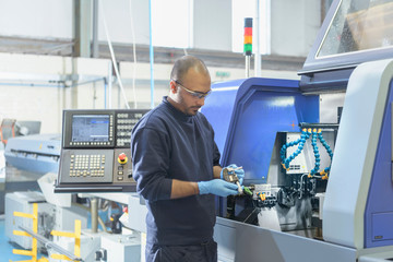 Engineer inspecting part for automatic lathe in engineering factory