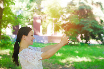 beautiful young European girl brunette takes a picture of herself and makes selfie in the city park. people, lifestyle, walking in the fresh air.