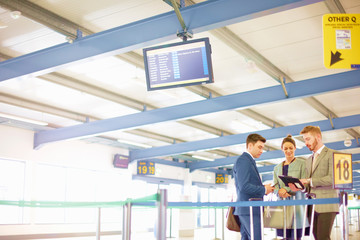 Businesswoman and men looking at digital tablet in airport