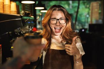 Fototapeta Portrait of a happy young barista girl in apron obraz
