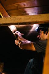 Electrician measuring beams in loft