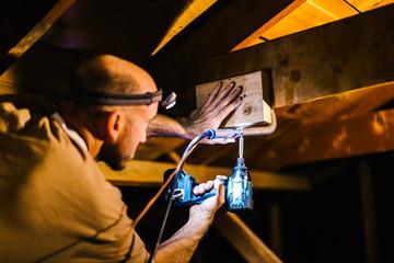 Electrician using head torch installing loft wiring