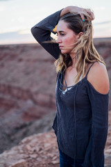 Young woman in remote setting, looking at view, holding hair off face, Mexican Hat, Utah, USA