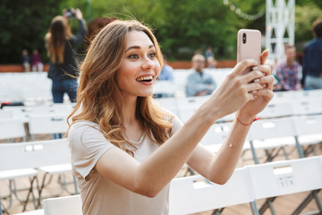 Excited young girl taking picture with mobile phone