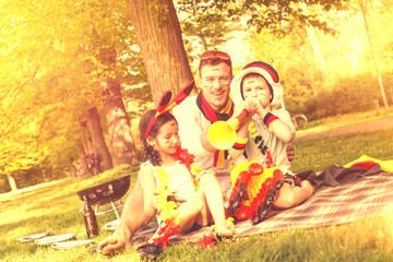 Familienvater mit Kindern im Park beim Grillen
