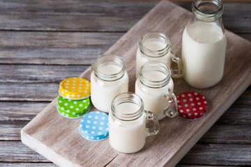 Milk jars with colorful caps on a cutting board