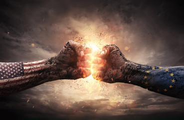 USA- UE embargo conflict, close up of two fists hitting each other over dramatic sky background with copy space