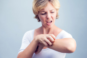 Woman Scratching an itch on white background . Sensitive Skin, Food allergy symptoms, Irritation
