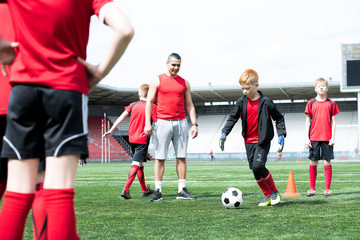 Full length portrait of junior football team practice, focus on red haired teenage boy leading ball with coach watching him, copy space
