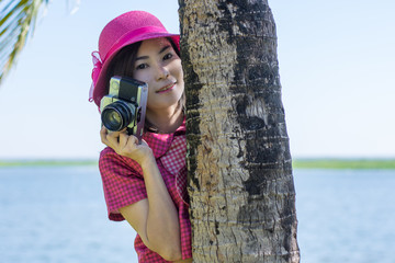 Happy young woman with vintage camera in the coconut park.